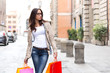 Pretty girl with glasses carrying shopping bags