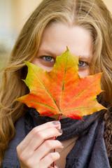 Junge Frau im Herbst mit buntem Ahornblatt vor dem Gesicht