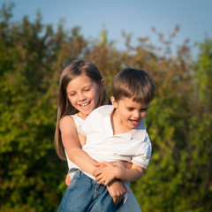 Young sister hugs her brother outdoors.