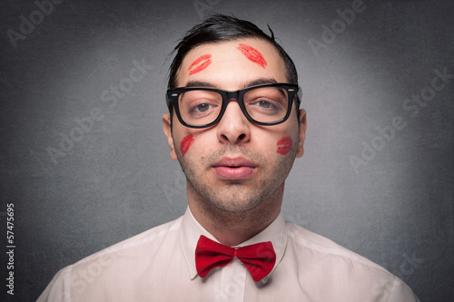 Portrait of young nerd with kiss imprints isolated on grunge bac