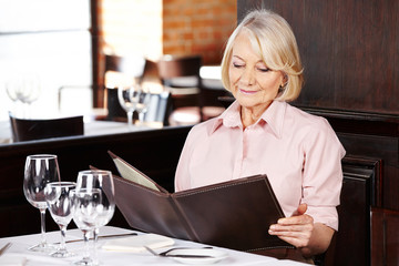 Senior woman reading menu in restaurant