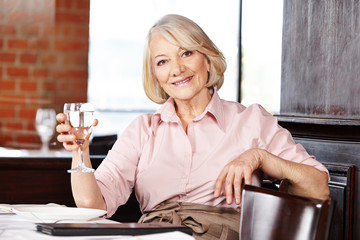 Senior woman drinking water in restaurant