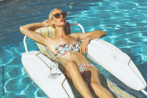 Blonde girl laying in the pool