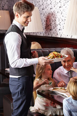 Waiter serving family in restaurant