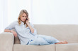 A worried looking woman lying on a couch is talking on her mobil