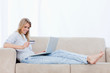 A woman lying on a couch with a laptop in front of her is holdin