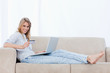 A woman holding a bank card is lying on a couch with a laptop in