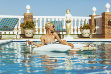 Blonde model relaxing in pool