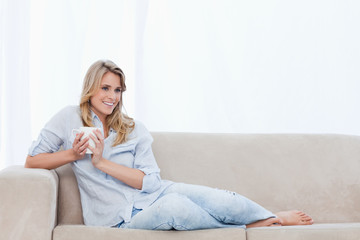 A smiling woman lying on a couch is holding a cup of coffee