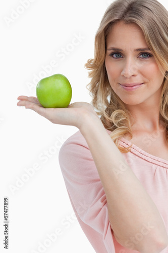 Young woman holding a green apple while looking at the camera