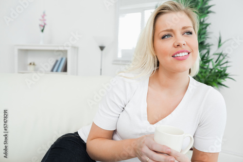 Woman seating on a sofa with a cup of coffee