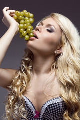 young beautiful blonde posing with grape, studio shot