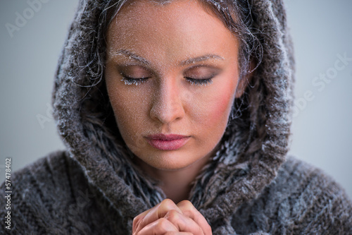 Woman praying. Wearing hoodie. Frost on her face