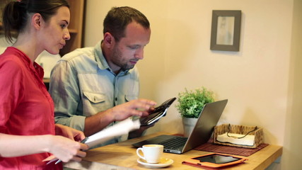 Young couple paying bills online on laptop computer