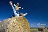 Father playing with son (7-9) on hay bale, arms outstretched, low angle view
