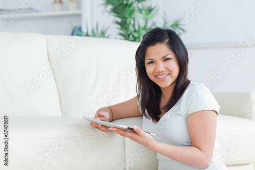 Woman sitting on the floor while holding a tactile tablet