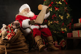 Portrait of happy Santa Claus reading Christmas letter or wish l