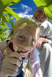 Girl (11-13) by grandfather looking through magnifying glass, low angle view