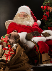 Santa Claus with a huge bag full of Christmas presents sitting i