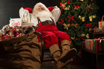 Santa Claus keeping his hands behind head while relaxing at home