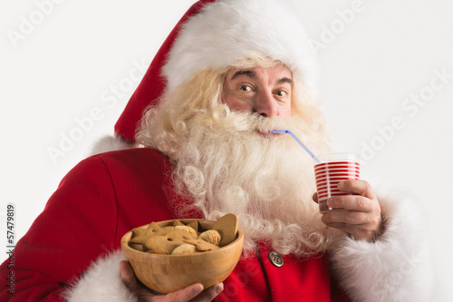 Portrait of Santa Claus Drinking milk from glass and holding bow