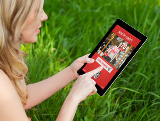 girl holds a tablet on a background of green grass and makes onl