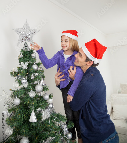 Daughter And Father Decorating Christmas Tree