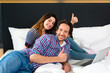 Young couple in Hotel in bed with wifi and computer