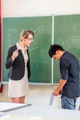 Lehrerin tadelt an Tafel Schüler in Klasse einer Schule