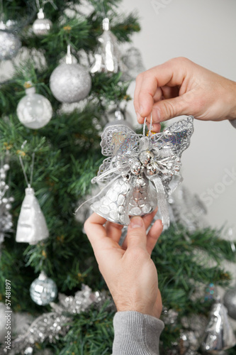 Man Holding Silver Bells In Front Of Christmas Tree