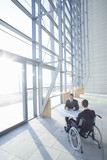 Businessman in wheelchair meeting with co-worker in modern lobby