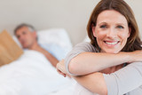 Smiling woman on bed with reading husband in the background