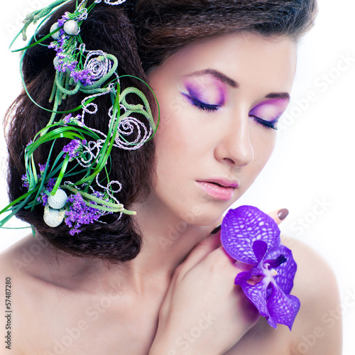 Beauty girl with orchid flowers and professional makeup