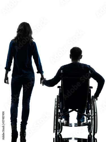 handicapped man in wheelchair  and woman holding hands silhouett