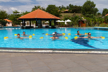 group doing aqua aerobics in swimming pool with dumbbells
