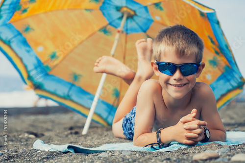 happy smiling kid is sunbathing on a beach