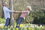 Smiling senior couple holding hands around tree trunk in sunny daffodil field