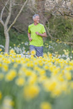 Smiling man jogging in sunny daffodil field