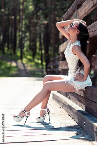 Outdoor portrait of young beauty woman in white short fashionabl