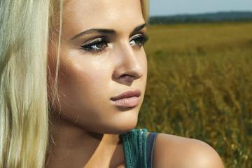 Beautiful blond girl on the field.beauty woman.nature background