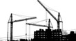 Silhouettes of two cranes near of building