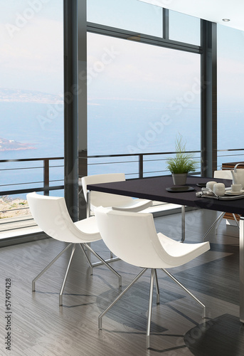 Modern dining table against floor to ceiling window with landsca
