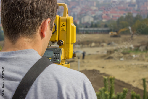 Land surveyor behind theodolite