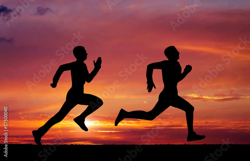 Silhouettes of two runners on sunset fiery background