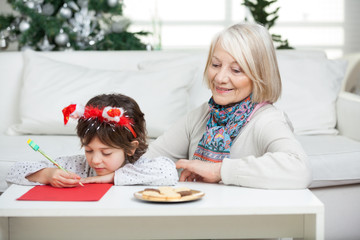 Grandmother Looking At Boy Writing Letter To Santa Claus