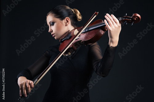 Beautiful young woman playing violin over black - 57502294