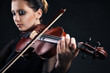 Beautiful young woman playing violin over black - 57502626