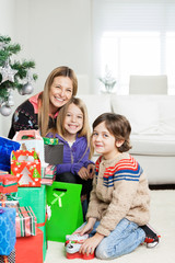 Mother And Children With Christmas Gifts