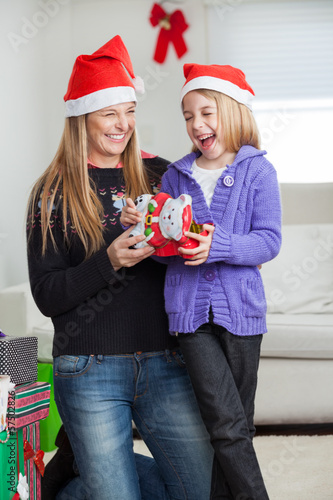 Cheerful Daughter And Mother With Christmas Present