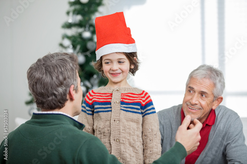 Father And Grandfather Looking At Son During Christmas